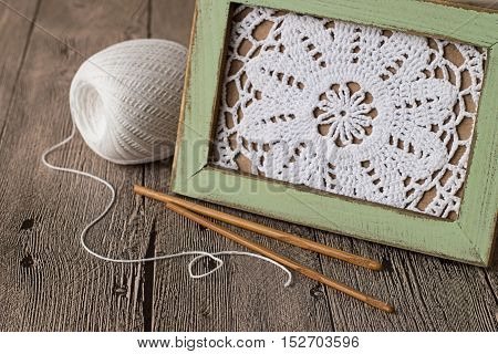 Openwork knitted napkin in a wooden frame, a ball of thread and crochet hooks on an old wooden table.