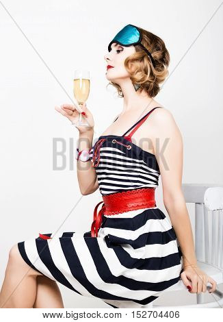 beautiful young woman in a striped dress holding a glass of champagne.