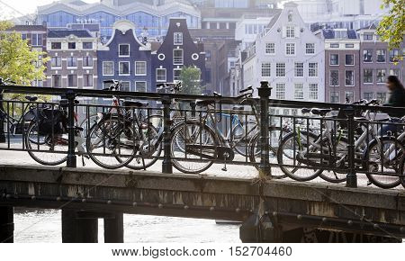 Bicycles attached to the railing of a bridge in Amsterdam