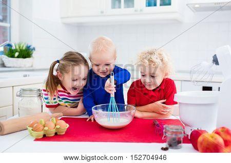 Kids Baking A Pie In White Kitchen