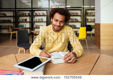 Hapyy african american young man with blank screen tablet sitting and studying in library