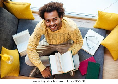 Top view of smiling african american young man reading book at home