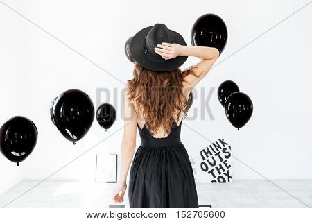 Back view of attractive young woman in black hat with air balloons standing over white background