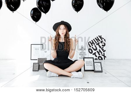 Funny pretty girl with black balloons pointing up and having an idea over white background
