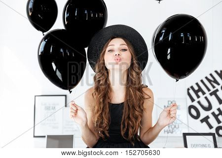 Cute lovely young woman with black balloons and posters sending a kiss over white background