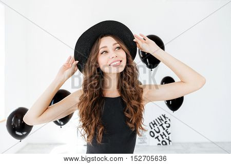 Cheerful cute young woman in hat standing and smiling over white background with black balloons