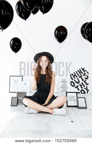 Portrait of happy charming girl with black balloons sitting with legs crossed over white background