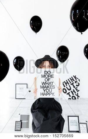 Cute amusing young woman in hat sitting and hiding behind white board over black balloons background