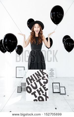 Cheerful amazed young woman with poster and black balloons standing and holding copyspace on palms over white background
