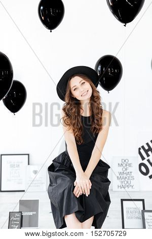 Portrait of happy beautiful young woman with posters and air balloons sitting over white background