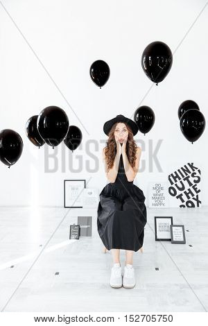 Amazed young woman sitting in black decorations with ballons and posters over white background