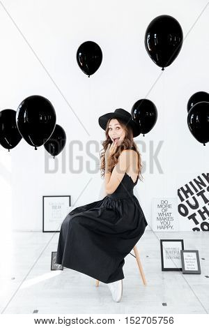Cheerful cute young woman in black dress and hat sitting near decorations with posters and balloons over white background
