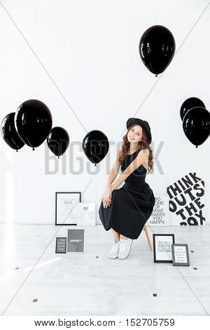 Cheerful pretty young woman sitting on chair near decorations with posters and balloons over white background