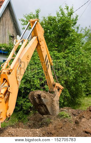 excavator is digging the ground in the countryside in summer