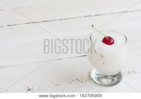 milk yogurt with berries cherries on white wooden background