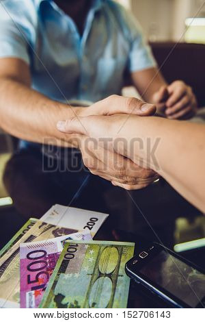 Two men shaking hands in cafe. Conclusion of the agreement bribe