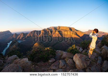Blyde River Canyon famous travel destination in South Africa. Tourist looking at panorama with binoculars. Last sunlight on the mountain ridges. Fisheye distorted view from above.