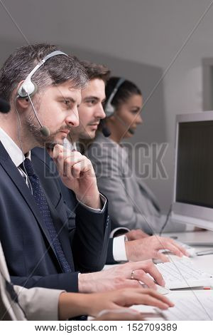 Cropped shot of an elegant business people wearing headsets and sitting at their desk