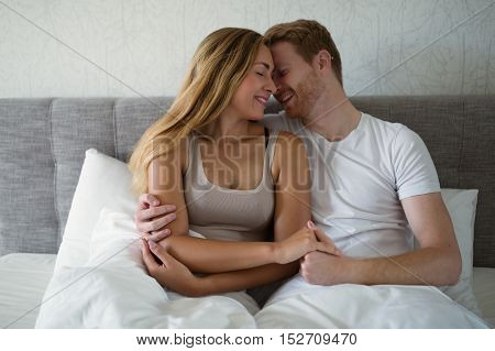 Romantic young beautiful couple in bed hugging