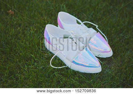 wedding shoes lying down on green grass. Retro style