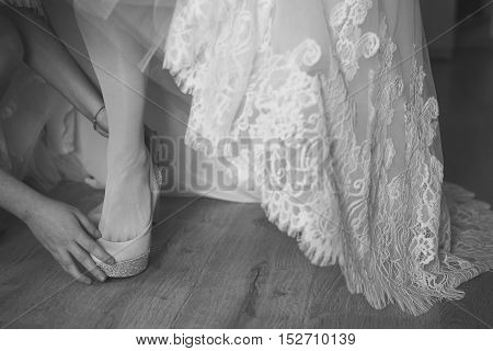 bridesmaid helping bride to put on elegant shoes. Black and white shot.