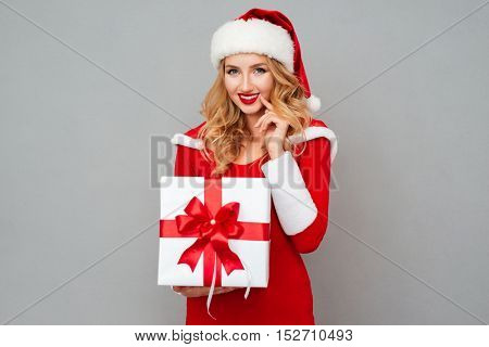 Smiling wondered woman in red santa claus dress holding xmas present isolated on the gray background