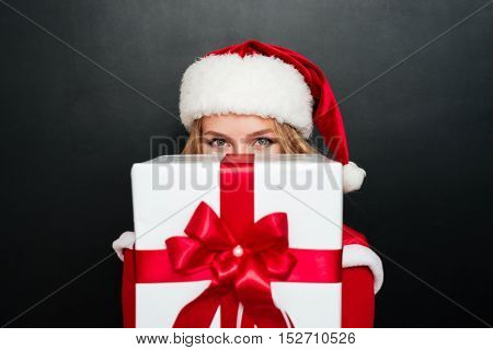 Excited blonde woman in red santa claus dress giving big gift box to camera isolated on the black background