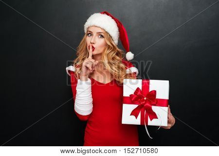 Attractive blond woman in santa claus dress and red hat holding big gift box and showing silence gesture isolated on the black background