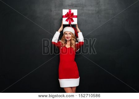 Beautiful young woman in red santa claus dress and hat holding gift box above her head isolated on the black background
