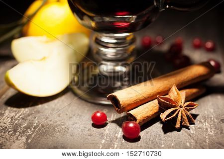 mulled wine with illicium and cinnamon on black background close-up