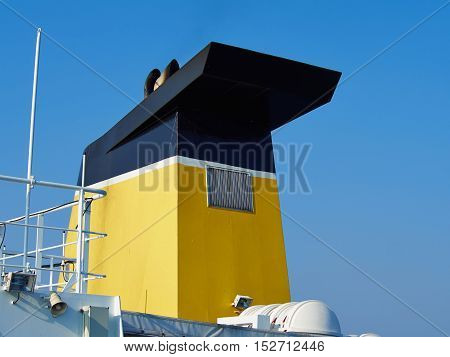 Black and yellow chimney of a cargo ferry ship with background of clear summer sky
