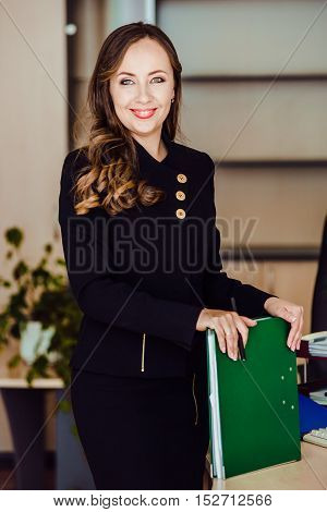 Coquettishly smiling businessman holding a folder in his hands itself