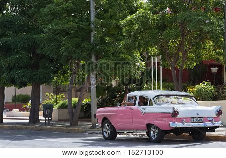 Varadero, Cuba - September 06, 2016: American rose Chevrolet classic car with white roof  on the street in Cuba - Serie Cuba 2016 Reportage