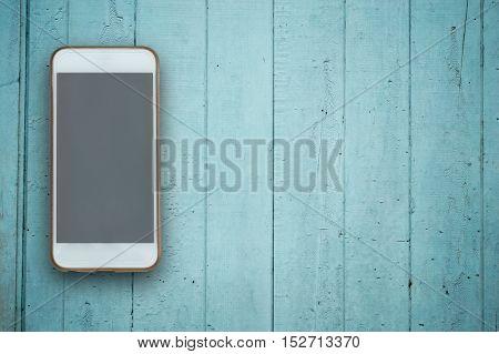 Blank screen phone on blue wood background.