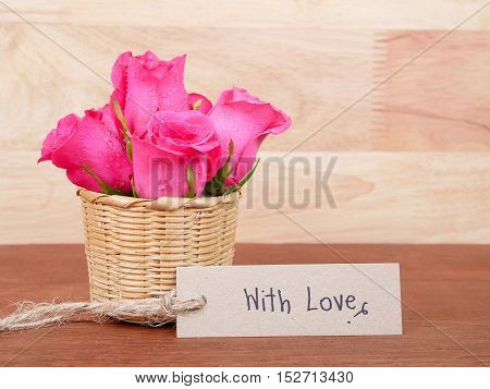 Pink rose flower in the basket and handwriting With love on brown label paper with wood background