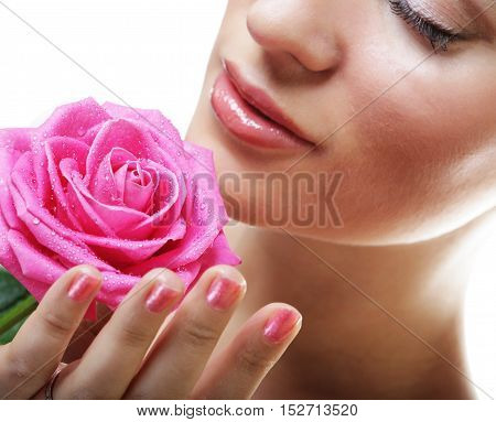 People, health and spa concept: beautiful  young woman with pink rose
