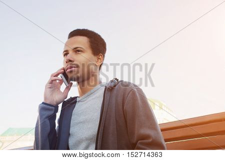 handsome young Afro American man in sport wear talking on mobile phone. Guy outdoors