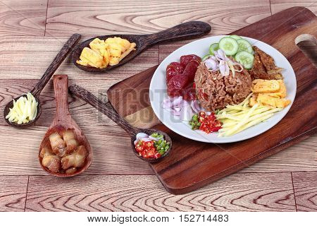 Thai food ,Fried jasmine rice with shrimp paste,(Kao Klok Kapi in Thai) served with green sour mango roll,Chinese sausage,crispy dried fish,shrimp,minced chili,shallots,stir sweet pork ,sliced cucumber and scrambled egg .