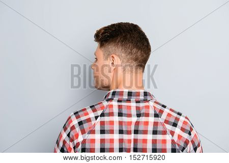 Back View Of Young Guy In Chekered Shirt  On Gray Background