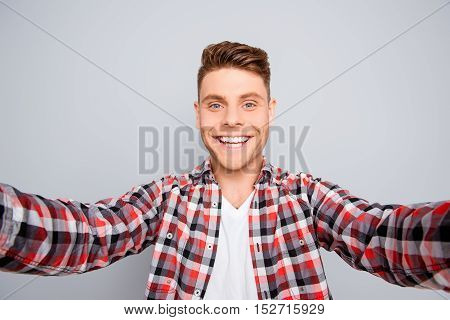 Happy Young Guy With Beaming Smile Making Selfie