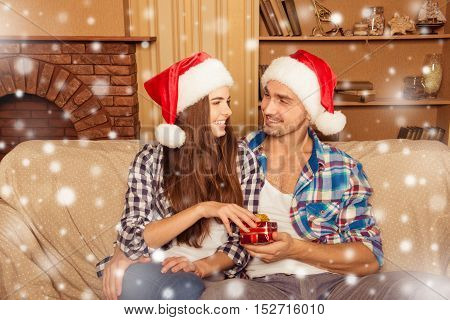 Happy Young Friends In Santa Hats Giving Christmas Presents