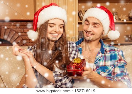 Handsome Man In Santa Hat Giving A Gift To His Girlfriend For Christmas