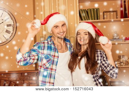Happy Smiling Lovers At Home Dressed In Santa Hats