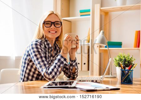 Smiling Woman Drinking Coffee And Dreaming At Workplace
