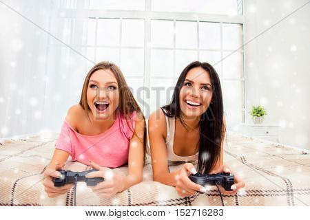 Happy Sexy Girls Lying In Bedroom With Joysticks On Xmas Holidays