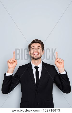 Portrait Of A Happy Young Man Pointing Up At Something Interesting
