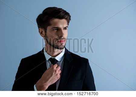 Portrait Of Serious Handsome Man In Suit Touching His Tie