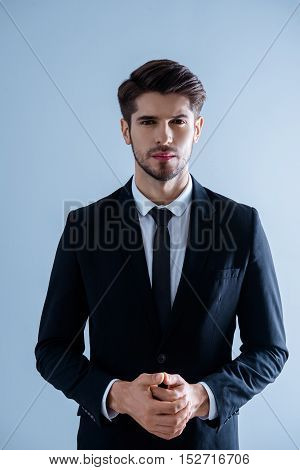 Portrait Of Serious Young  Successful Businessman With Clasped Hands
