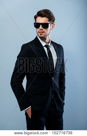 Portrait Of Brutal Handsome Man In Black Glasses Holding Hands In Pockets