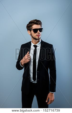 Young Confident Brutal Businessman In Black Suit And Spectacles